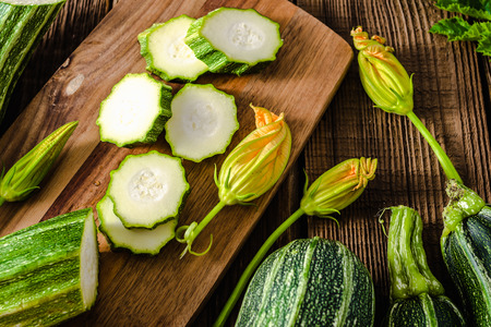 Fresh zucchini and slices of zucchinis on wooden table. Sliced courgette, healthy vegan diet or vegetarian food, cooking concept. Stockfoto