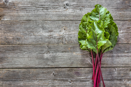 Fresh leaves of beets, green vegetables on local farmer market, freshly harvested beet leaf bunch on wooden background Stock Photo