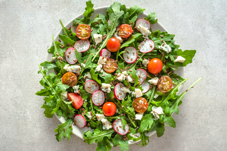 Diet food. Fresh salad with arugula leaves on plate, top view, healthy nutrition and vegetarian food concept