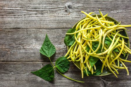 Fresh bean, yellow organic beans on plate on wooden table