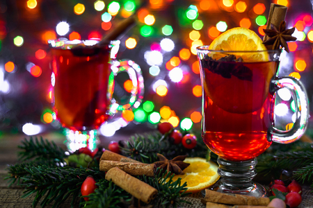 Christmas mulled wine with fruit and spices. Winter holiday drink on lights background.