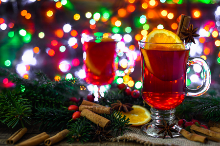 Christmas mulled wine with spices on wooden table. Hot drink on lights background.