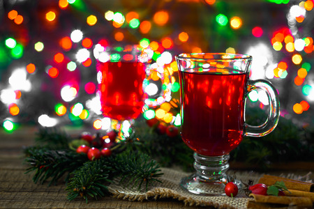 Hot mulled wine on table, magic atmosphere under Christmas tree with lights Foto de archivo