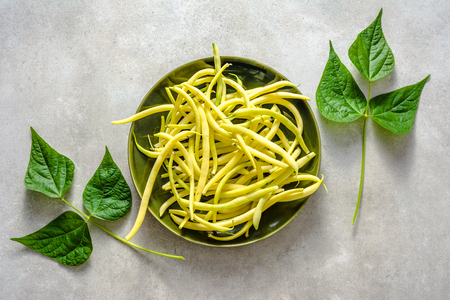 Fresh bean, organic vegetables for cooking, freshly harvested yellow beans on plate, top view Stock Photo