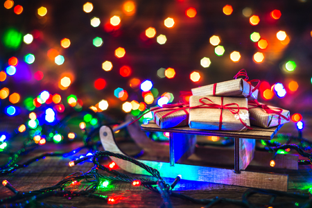 Christmas gifts on light background. Blur lights and magic atmosphere under tree with gift boxes on santa sleigh. Stok Fotoğraf