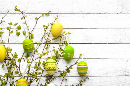 Easter decoration with colored eggs on white wooden background