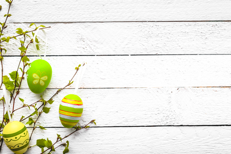 Easter egg on white wooden background. Spring decoration with painted eggs hanging on branch.