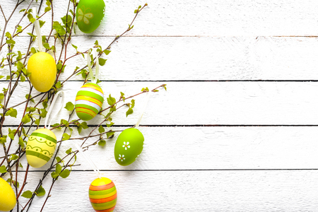 Easter background with colored eggs on white wooden table