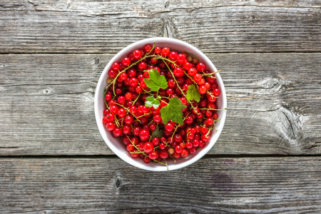 Fresh red currant in a bowl on wooden table