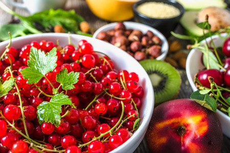 Red currant on table with food. Healthy super foods for breakfast, bowls with organic fresh fruits and nuts. Vegetarian diet concept.
