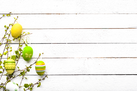 Easter background with easter eggs and spring branch of birch tree