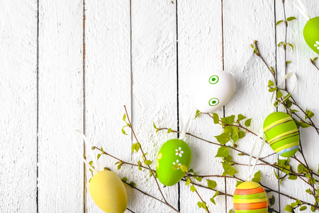 Spring easter eggs background, seasonal colored eggs on white wooden boards