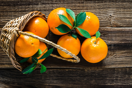 Basket with fresh oranges on farmer market, orange fruit, top view on wooden background