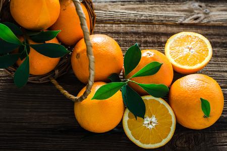 Naranjas orgánicas frescas en una canasta sobre mesa de madera. Fruta naranja en el mercado.