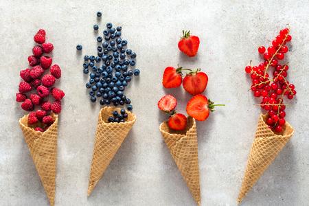 Berry fruit in waffle cones. Fresh berries, healthy dessert, summer concept. Foto de archivo - 116461536