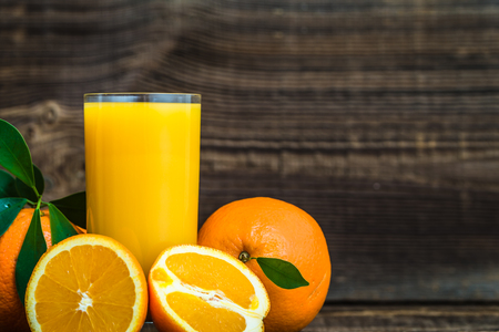 Freshly squeezed orange juice and fresh oranges on wooden table
