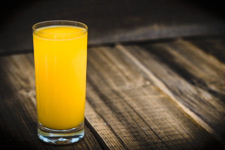 Fresh juice in a glass. Orange juice on wood. Stockfoto