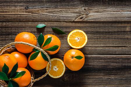 Cesto con arance su fondo di legno. Arancia fresca dell'azienda agricola sul mercato.