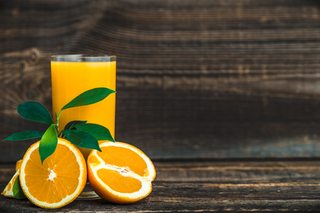 Juicy oranges and fresh juice on wooden table