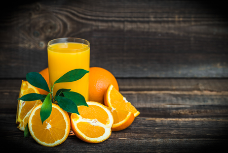 Fresh orange juice in a glass with freshly squeezed oranges on wooden table