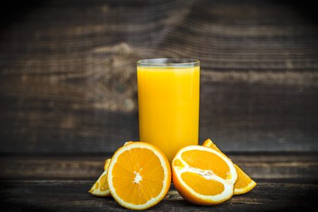 Fresh orange and squeezed orange juice on table