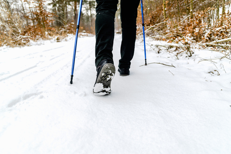 Woman hiking in snow. Boots and legs detail. Outdoor activity, winter walk in snow with nordic walking sticks.