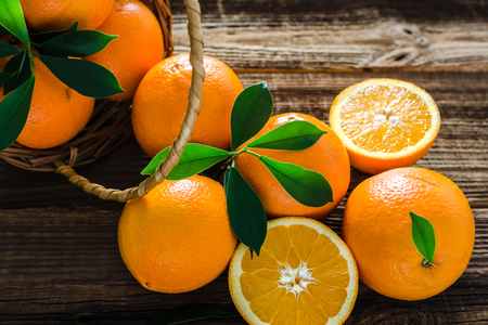 Verse sinaasappelen oogst. Biologisch oranje fruit in een mand op houten ondergrond. Stockfoto