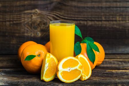 Freshly squeezed orange juice in a glass. Fresh juice on wood. Foto de archivo - 117588595