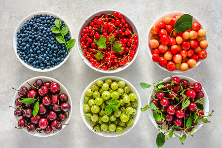 Bowls with berry. Fresh assortment of berries, variety of fruits in a bowls. Cherry, red strawberry, blueberry and currant. Archivio Fotografico