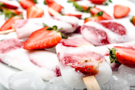 Natural juicy strawberry popsicles with yogurt or ice cream with berries.