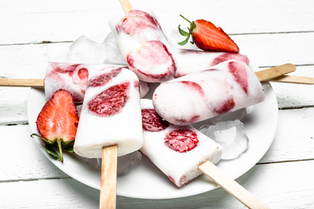 Fruit ice cream on stick. Strawberry popsicle with yogurt and frozen berries.