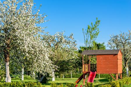 Kinderspielhaus oder Holzschuppen im Garten zwischen blühenden Bäumen im Frühling Standard-Bild