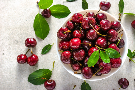 Sweet cherries on plate, top view. Fresh red cherry with leaves.