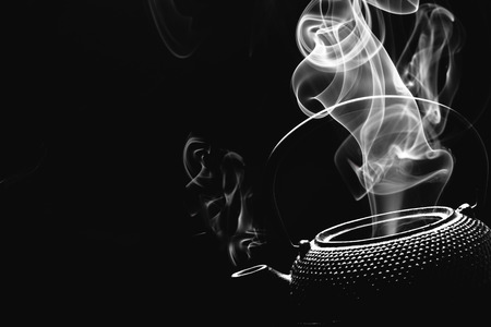 Antique teapot with steaming hot tea on black background. Archivio Fotografico - 120320622