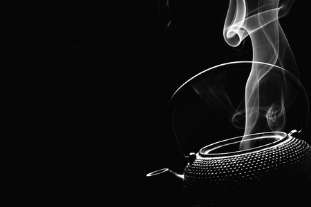 Rustic teapot on black background. Steaming tea kettle. Cooking concept.