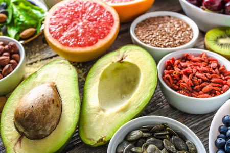 Fresh avocado and other healthy food. Organic breakfast containing super foods. Vegan nutrition like nourishing fruit, assorted berries and seeds. Stock Photo