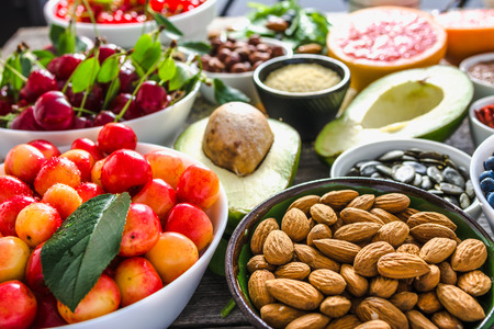 Bowl with almond, sweet cherry, fresh fruit and other healthy food. Organic breakfast with vegan nutrition. Superfoods collection on table. Stock Photo