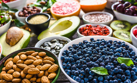 Bowl with almonds, bilberry, fresh fruit and other healthy food. Organic breakfast with vegetarian nutrition. Super foods collection on table. Stock Photo