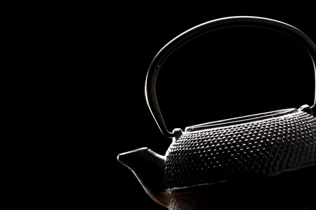 Teapot on black background