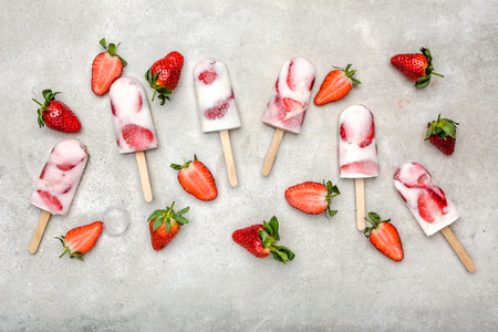 Fresh fruit popsicles. Juicy homemade ice cream with strawberry fruits, snack food, refreshing frozen dessert for summer.