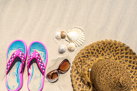 Holiday vacation accessories on the beach, top view, flat lay on sand background