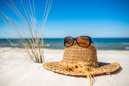 Hat and sunglasses. Accessories for sun protection on the sea beach, summer holiday vacation over Baltic, Poland 写真素材
