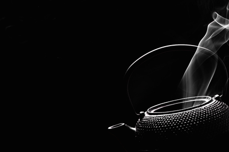 Rustic tea pot on black background. Steaming teapot. Cooking concept.