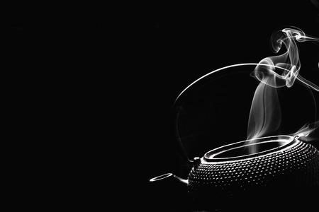 Antique rustic teapot on black background. Steaming tea pot. Cooking concept. Archivio Fotografico - 122288156