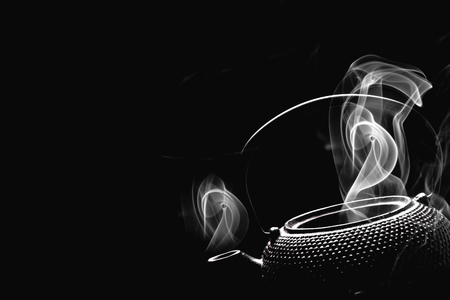 Teapot with boiling water. Steaming tea kettle on black background. Cooking concept. Stock Photo