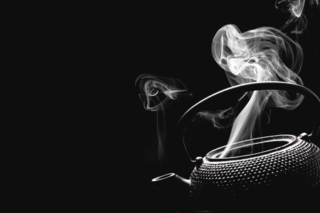 Antique tea pot. Steaming teapot on black background. Cooking concept. Stock Photo
