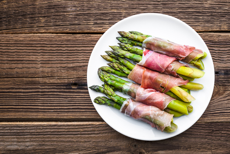 Cooked asparagus. Appetizer with vegetable and meat, italian dish on plate. Stock Photo
