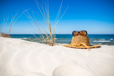 Sunny holiday beach, summer vacation concept - sun hat and sunglasses on white sand, Baltic Sea, Poland 写真素材