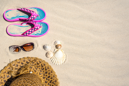 Summer background with vacation accessories on the beach, top view on sand