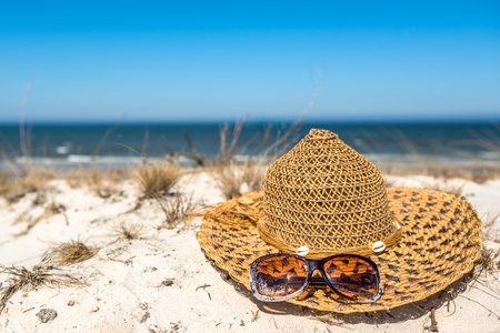 Blue sky and white sand vacation sea beach with sun hat and sunglasses, summer holiday landscape Zdjęcie Seryjne - 122552425